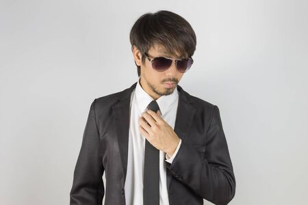 Portrait Businessman in Black Suit and Black Eyeglasses Touch Necktie. Portrait businessman wear white shirt and suit in smart pose style