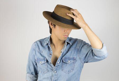 Portrait Man in Jeans Shirt or Denim Shirt Fashion Touching Hat. Jeans shirt or denim shirt fashion for men on grey background