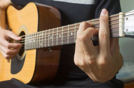 Guitar Player Hand or Musician Hand in F Major Chord on Acoustic Guitar String with soft natural light in side view