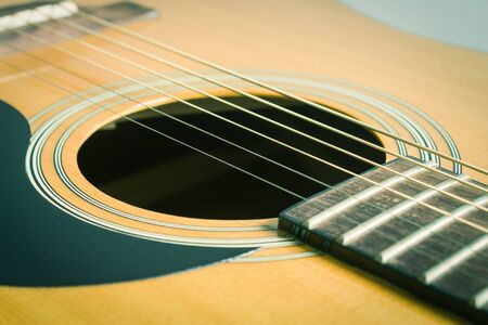 Sound Hole and Acoustic Guitar String and Pick guard and Fingerboard and Fret in Crosswise View