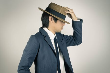 Young Asian Portrait Businessman in Navy Blue Suit Touch Hat at Side View on Grey Background Stock Photo