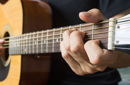 Guitar Player Hand or Musician Hand in C Major Chord on Acoustic Guitar String with soft natural light in side view