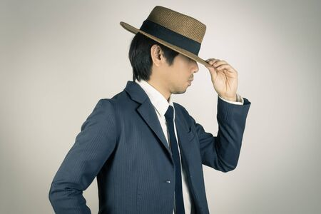 Young Asian Portrait Businessman in Navy Blue Suit Touch Hat Brim at Side View on Grey Background