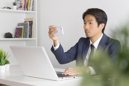 Asian Businessman Take Photo or Selfie by Smartphone in front of Laptop monitor in Office. Asian businessman relax time