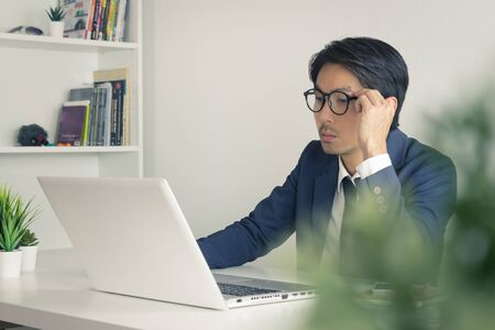 Asian Financial Advisor or Asian Consulting Businessman Analyze Financial Data in front of Laptop. Asian financial advisor or Asian consulting businessman working in office