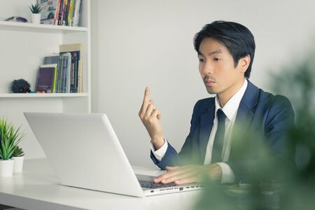 Asian Businessman Angry Partner and Show Middle Finger in front of Laptop. Vulgarity of Asian businessman in pressure condition Banco de Imagens