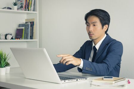 Asian Financial Advisor or Asian Consulting Businessman in Suit Recommend Customer Via Internet in Office. Asian financial advisor or Asian consulting businessman pointing laptop monitor