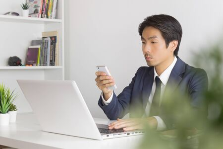 Asian Financial Advisor or Asian Consulting Businessman Use Smartphone and Laptop in Office. Asian financial advisor or Asian consulting businessman contact with customer Banco de Imagens