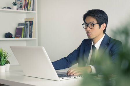 Asian Financial Advisor or Asian Consulting Businessman Seriously Working in front of Laptop. Asian financial advisor or Asian consulting businessman working in office Banco de Imagens
