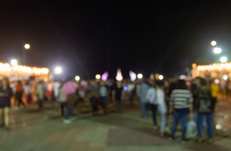 Blurred Crowd on Street and Light on Night Background. Crowd blurred focus in standing posture with colorful light