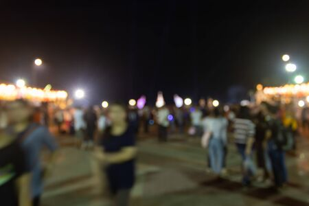 Blurred Crowd on Street and Light in Night Scene with Human on Foreground. Crowd blurred focus in standing posture with colorful light