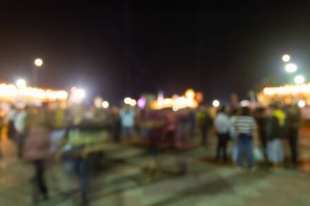 Blurred Crowd and Light in Night Scene and Brown Shirt Human at Left Frame. Crowd blurred focus in standing posture with colorful light Banco de Imagens