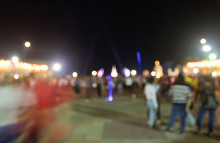 Blurred Crowd on Street and Light in Night Scene and Human on Foreground. Crowd blurred focus in standing posture with colorful light
