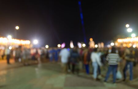 Blurred Crowd and Light in Night Scene and White Shirt Human at Center Frame. Crowd blurred focus in standing posture with colorful light Banco de Imagens