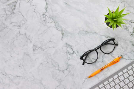 Modern Clean Flat Lay or Top View Office Desk or Office Table and Office Supplies as Computer Keyboard,Pen,Glasses,Office Plants on Marble Minimalist Background Banco de Imagens