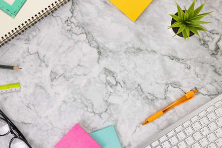 Modern Clean Flat Lay or Top View Office Desk or Office Table and Stationery as Computer Keyboard,Pen,Stick Note,Office Plants,Glasses,Spiral Notebook,Pencil,Ruler on Marble Minimalist Background Banco de Imagens