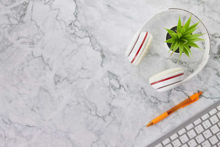 Modern Clean Flat Lay or Top View Office Desk or Office Table and Office Supplies as Computer Keyboard,Pen,Headphone,Office Plants on Marble Minimalist Background