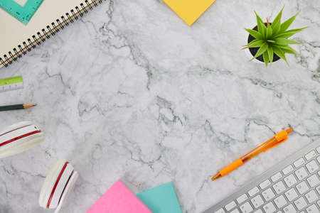 Modern Clean Flat Lay or Top View Office Desk or Office Table and Stationery as Computer Keyboard,Pen,Stick Note,Headphone,Office Plants,Spiral Notebook,Pencil,Ruler on Marble Minimalist Background Banco de Imagens