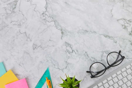 Modern Clean Flat Lay or Top View Office Desk or Office Table and Office Supplies as Computer Keyboard,Pen,Glasses,Stick Note,Triangle Ruler on Marble Minimalist Background