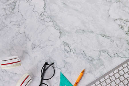 Modern Clean Flat Lay or Top View Office Desk or Office Table and Office Supplies as Computer Keyboard,Pen,Glasses,Headphone,Triangle Ruler on Marble Minimalist Background