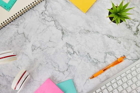 Modern Clean Flat Lay or Top View Office Desk or Office Table and Stationery as Computer Keyboard,Pen,Stick Note,Office Plants,Headphone,Spiral Notebook,Ruler on Marble Minimalist Background Banco de Imagens