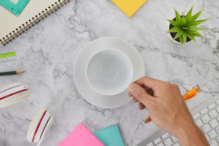 Flat Lay or Top View Hand Hold Coffee Cup on Marble Office Desk or Office Table Include Stationery as Computer Keyboard,Pen,Stick Note,Headphone,Office Plants,Spiral Notebook,Ruler,Pencil Banco de Imagens