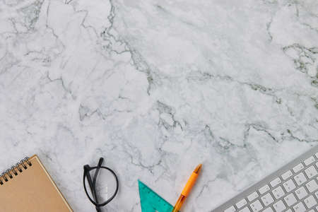 Modern Clean Flat Lay or Top View Office Desk or Office Table and Office Supplies as Computer Keyboard,Pen,Glasses,Spiral Notebook,Triangle Ruler on Marble Minimalist Background
