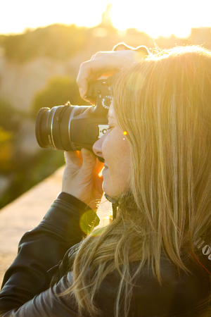 blonde girl takes photos with reflex from a vantage point in Barcelona, Spain