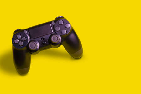 Video game joystick isolated in yellow background.
