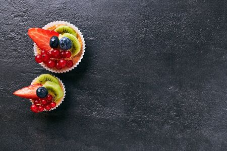 Fresh homemade fruit tart with strawberries, kiwi, blueberry, on dark stone background. Top view scene. Side border with copy space.