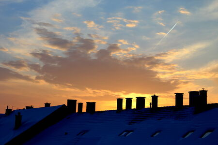 strenghten: Dawn in the city. The rising sun is shining behind the clouds. The orange and blue colour strenghten each other. The roof of the houses in the front shows this picure was shoot in the city. The nature and the houses make good contrast. Stock Photo