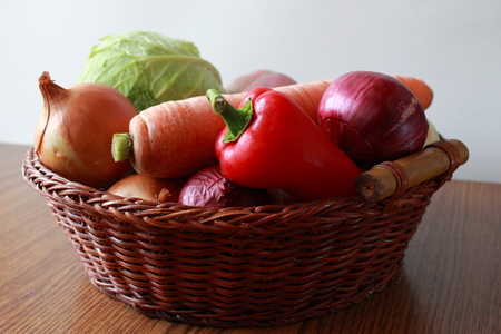 Fresh vegatables in a basket on the table. Stock Photo