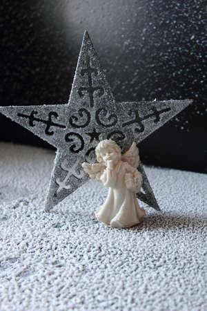 sentiment: Simple composition with angel and star on the snow.