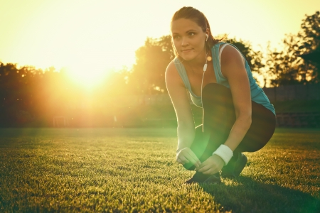 recreational sport: Young woman preparing to run in a playground, sunset in the background Stock Photo