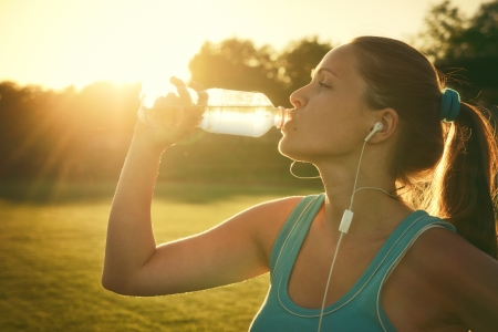 Young woman drinking water after run photo