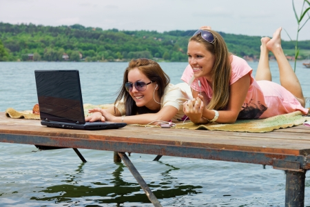 Two cheerful young woman use a laptop on holidays photo
