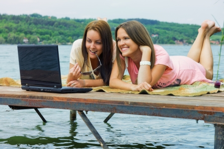 communicaton: Two cheerful young woman use a laptop on holidays