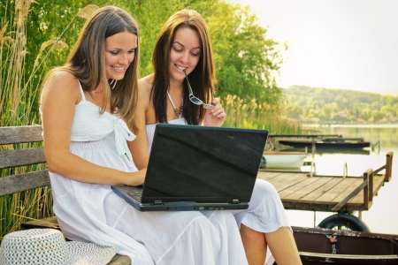 Two young woman are sitting on a pier and use theirs laptop to surfing on the internet photo