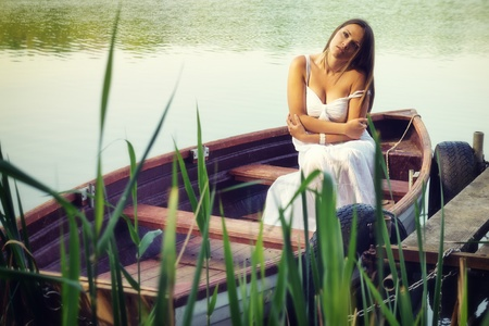 decolletage: Beautiful young sad woman sitting in a boat