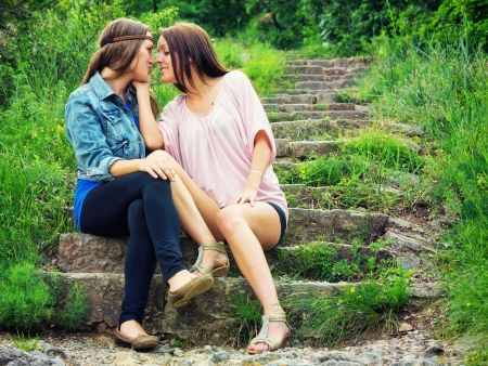 lesbian girls: Two young lovers sitting on stone stairs Stock Photo