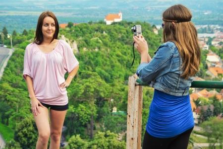 젊은 여자가 그녀의 아름다운 여자 친구에서 사진을 찍어