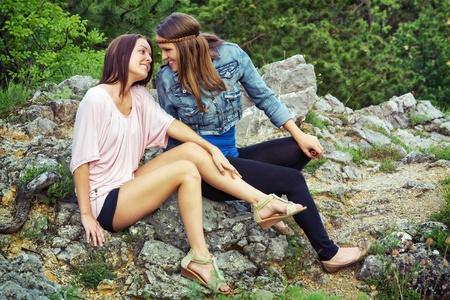 lesbianas: Dos jóvenes mujer sentada sobre la roca