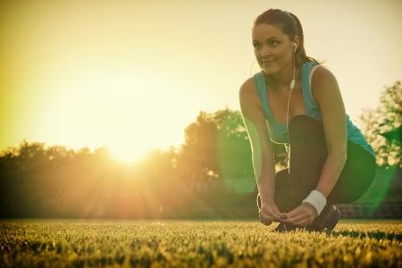 Giovane donna prepara a correre in un parco giochi, tramonto sullo sfondo Archivio Fotografico - 22181327