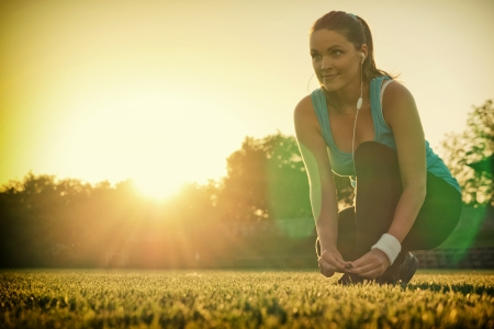 Young woman preparing to run in a playground, sunset in the background Banque d'images
