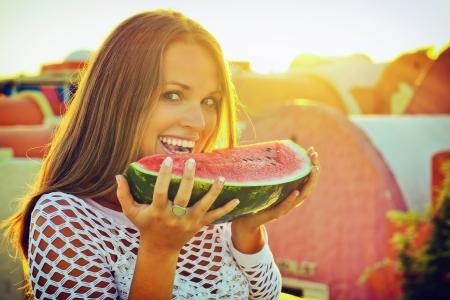 그녀의 휴일에 수박을 먹는 아름다운 젊은 여자