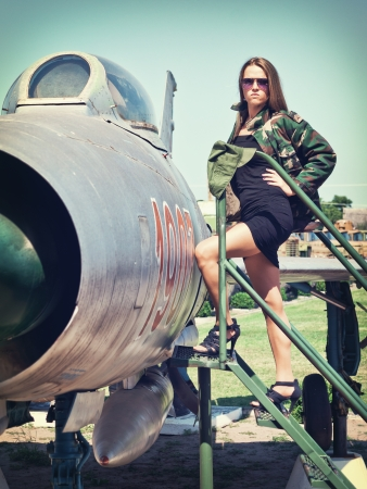 Beautiful young woman getting ready to get in an old fighter bomber