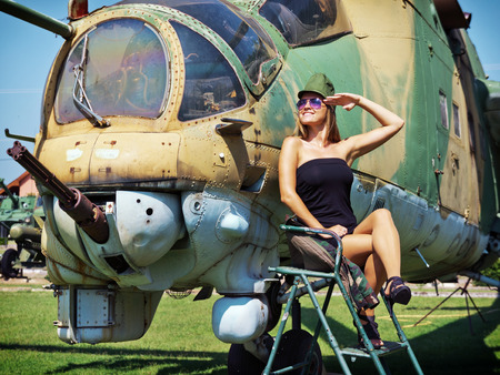 army girl: Beautiful young woman salute to the veteran attack helicopter