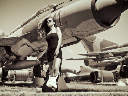 Beautiful young woman standing before a veteran fighter bombers with her guitar
