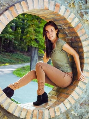 arrodillarse: La muchacha hermosa, apasionada está en el círculo de ladrillo