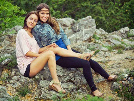 lesbian girls: Two young woman sitting on rock Stock Photo
